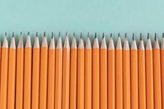 Border of sharpened orange pencils, with copy space. Border of sharpened orange pencils. Flat lay on a textured background, with copy space royalty free stock images
