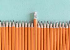 Border of orange sharpened pencils, with one eraser in the middle stock images