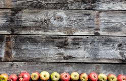 Border of organic apples on old genuine wood, flat lay. Bottom border made of red and yellow organic apples on old genuine wooden background for fall diet Stock Photo
