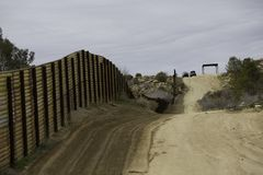 Border Patrol Vehicles Near Barrier Wall in California. Border Patrol Vehicles near wall seperating the United States from Mexico stock photos