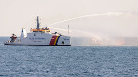 Border police coast guard saving boat in flames Stock Photography