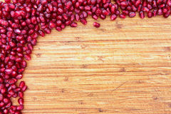 Border of pomegranate seed on a wood background Stock Photos