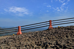 Border rack fence on rock cliff. With clear blue sky royalty free stock photo