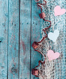 Border of romantic hearts in fishing net. Border of romantic pink and white hearts in fishing net with an edge decoration of corks in vertical format on rustic stock photo