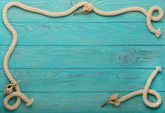 Border with rope and sea shells on a turquoise wooden background Stock Photography