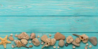 Border with rope, stones, sea shells and starfish on a turquoise. Wooden background. Top view Royalty Free Stock Images