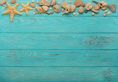 Border with rope, stones, sea shells and starfish on a turquoise. Wooden background. Top view Royalty Free Stock Photos
