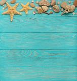 Border with rope, stones, sea shells and starfish on a turquoise. Wooden background. Top view Stock Photo