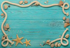 Border with rope, stones, sea shells and starfish on a turquoise. Wooden background. Top view Stock Photos