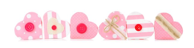 Border of rustic pink Valentines heart-shaped gift boxes over white Stock Images