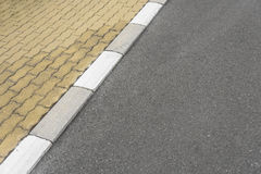 Border sidewalk and the asphalt road. Royalty Free Stock Photos