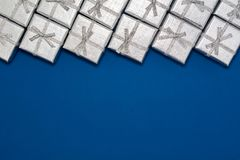 Border of silver shiny gifts on blue background. New Year`s and Christmas decorations Stock Photos