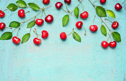Border of sweet cherries on branch with green leaves on light blue background, top view, place for text. Summer fruits and berries concept Royalty Free Stock Image