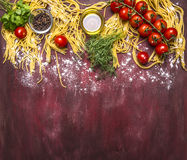 Border ,with text area,  raw pasta with tomatoes, flour, butter, black pepper, herbs and salt on wooden rustic background top view Stock Photos