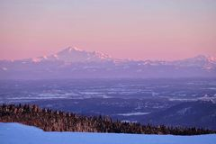 Border between United States and Canada. Snow capped mountain at sunset. View from Grouse Mountain to Mount Baker, US. North Vancouver. British Columbia. Canada Royalty Free Stock Image