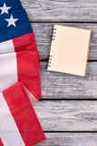 Border from USA flag and notebook. Top view on folded American flag, opened notepad on wooden background with copy space, vertical image Royalty Free Stock Image