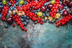 Border of Various summer berries on blue rustic background. Top view Royalty Free Stock Images