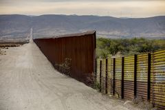 Border Wall Section Between United States and Mexico. A lengthy section of the United States border wall with Mexico in California stock photo