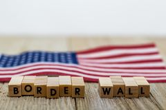 Border Wall USA concept with American flag on white background and wooden board. Protection. Government. Politics stock image