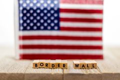 Border Wall USA concept with American flag on white background and wooden board. Protection. Government. Politics royalty free stock photo