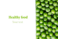 Border of wet fresh green peas in water closeup on white background. Stock Photos