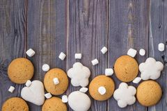 Border of white and brown gingerbread with marshmallows on wooden background Stock Images