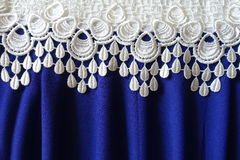 A border of white lace over blue fabric with folds. A border of white lace over electric blue fabric with folds stock image
