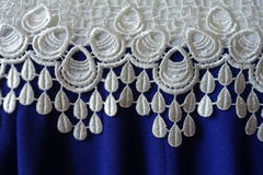 A border of white lace over blue fabric with pleats. A border of white lace over electric blue fabric with pleats stock image