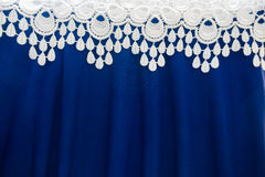A border of white lace over bright blue fabric. A border of white lace over electric blue fabric royalty free stock images