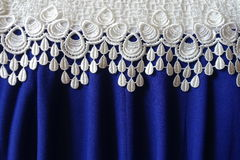 Border of white lace over draped blue fabric. Border of white lace over draped electric blue fabric stock photos