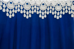 Border of white lace over folded blue fabric Royalty Free Stock Photography