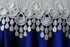 A border of white lace over rippled blue fabric. A border of white lace over rippled electric blue fabric royalty free stock images