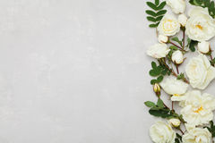 Border of white rose flowers and green leaves on light gray background from above, beautiful floral pattern, flat lay