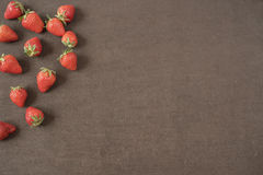 Border of whole fresh ripe red strawberries arranged on left sides on a dark textured slate background with copyspace. Fresh berry Stock Photo