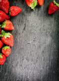 Border of whole fresh ripe red strawberries stock photography