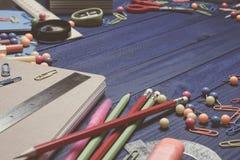 Bordi blu del fondo che si trovano sullo scrittorio dei rifornimenti di scuola della cancelleria: le matite, penne, taccuino, rig fotografia stock libera da diritti
