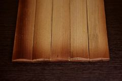 Bordi bruciati leggeri su un fondo di legno scuro immagini stock