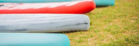Bordi del SUP che si trovano sull'erba dall'INSEGNA del fiume, del lago o del mare, FORMATO LUNGO immagini stock
