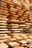 Bordi di legno impilati ordinatamente fuori di una falegnameria industriale immagini stock
