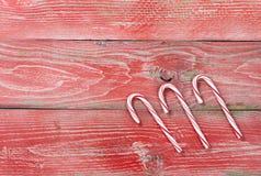Bordi di legno rossi rustici con i bastoncini di zucchero per il decorati di Natale Immagini Stock