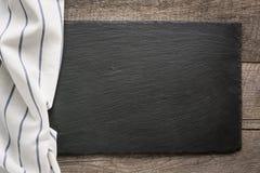 Bordi di legno rustici, tovagliolo bianco barrato con e piatto nero dell'ardesia con lo spazio della copia per il vostro menu o r Fotografie Stock Libere da Diritti