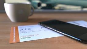 Bordkarte zu Medina und Smartphone auf dem Tisch im Flughafen beim Reisen nach Saudi-Arabien stock footage