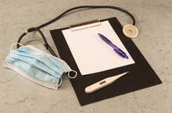 Bordlägga doktorn, termometern, stetoskopet, maskeringen, kulspetspennan, minnestavlan för att skriva royaltyfria foton