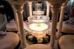 Bordlägga garnering av champagnespringbrunnen i ljus och bröllopstårta Royaltyfri Fotografi