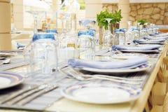 Bordlägga inställningen med överflöd av restaurangexponeringsglas och bestick Arkivfoto