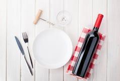 Bordlägga inställningen med den tomma plattan, vinexponeringsglas och rött vinflaskan Royaltyfria Bilder
