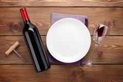 Bordlägga inställningen med den tomma plattan, vinexponeringsglas och rött vinflaskan Royaltyfri Foto