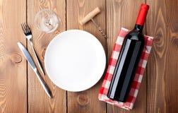 Bordlägga inställningen med den tomma plattan, vinexponeringsglas och rött vinflaskan Arkivbilder
