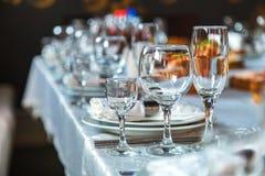 Bordlägga inställningen med exponeringsglas, plattor, servetter och mat Royaltyfri Fotografi