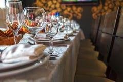 Bordlägga inställningen med exponeringsglas, plattor, servetter och mat Fotografering för Bildbyråer